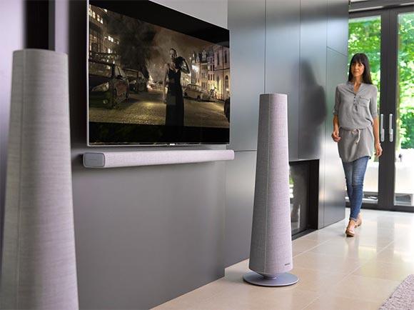 Une femme dans son salon marche vers son système home-cinéma composé de deux enceintes Citation Tower et d'une barre de son Citation Bar.